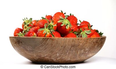 Strawberry in a wooden bowl rotates on a turntable, seamless...