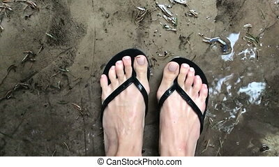 women's feet in slippers in the rain top view