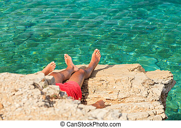 Young tourists sunbathe on mediterranean rocky beach