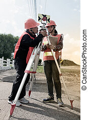Surveyor or Engineer making measure setting a prism reflector with partner on the field.