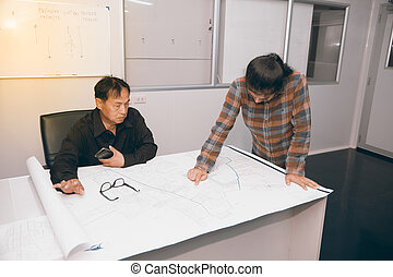 Architect and construction engineer or surveyor discussing plan and map in office room.