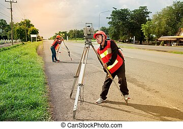 Surveyor or Engineer making measure with partner on the field.
