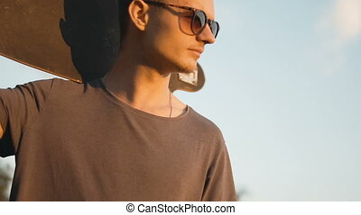 Skateboarder Man at Sunset - Young man wears sunglasses...