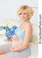Young happy pregnant woman sitting on couch in blue lace...