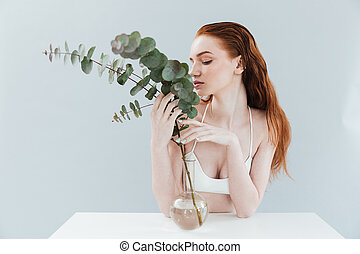 Young redhead girl holding eucalyptus - Fashion portrait of...