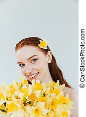 Close up portrait of a redheaded woman holding narcissus flowers