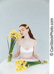 Young redheaded woman holding two bouquets of narcisuss -...