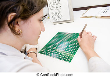 integrated microcircuit chip worker - Woman in white uniform...