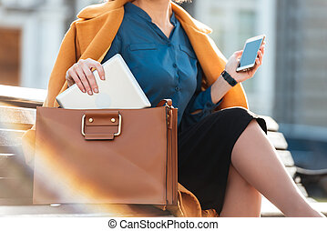 Cropped image of a woman in coat holding mobile phone -...