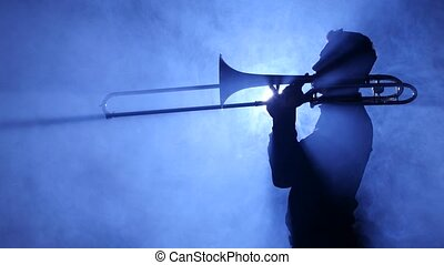 Trumpeter man in spotlight in smoky studio plays on...
