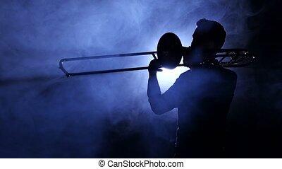 Man in spotlight in smoky studio plays on trombone, silhouette