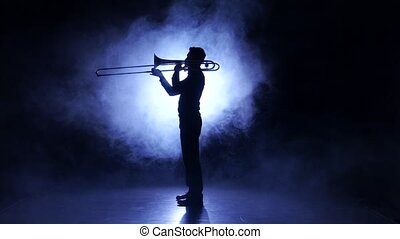 Trombone man in smoky studio playing on wind instrument,...