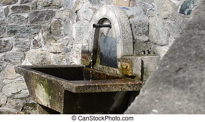 Clear and cold water flowing from metal pipe, fountain,...