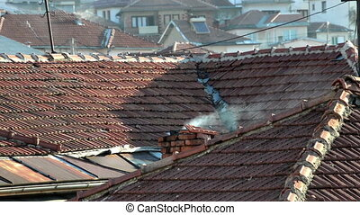 Smoke coming from chimney on house roof top