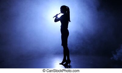Melody performed by musician girl playing flute. Silhouette,...
