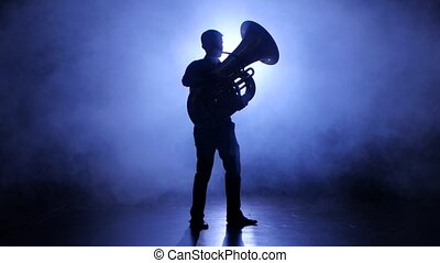 Trumpeter man in spotlight in smoky studio plays on tuba,...