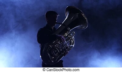 Musician in a smoky studio playing in a tuba, silhouette -...