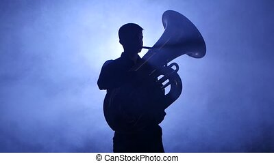 Trumpeter in spotlight in smoky studio plays on tuba....