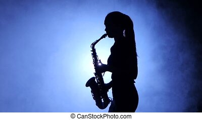 Woman in spotlight in smoky studio plays on saxophone,...