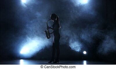 Instrumentalist woman plays on wind instrument saxophone...