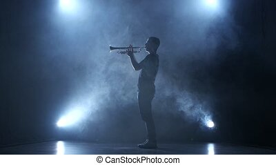 Trumpeter man in smoky studio and in spotlight playing melody