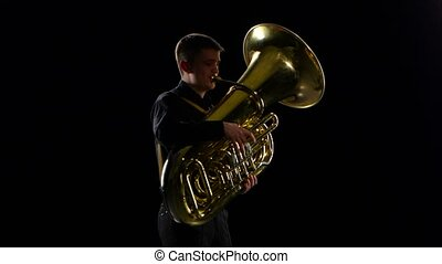 Man plays on the tuba slow melody. Black studio background -...