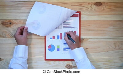 Businessman Checks Annual Report And Stock Statistics On...