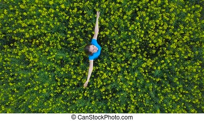 Young woman with arms outstretched in a yellow canola field...