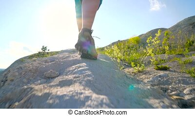 Legs of woman in tourist boots close-up. Hiking with a...