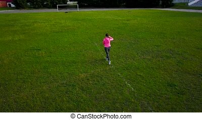 Woman runs through the stadium at sunset, view from the top...
