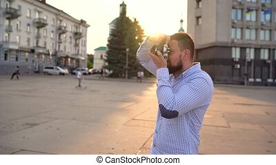 Man is walking around the city and taking photos of sights on a film camera