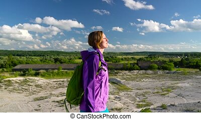 Woman is traveling with a backpack over hilly terrain....
