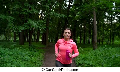 Woman runs through the forest - Young woman runs through the...