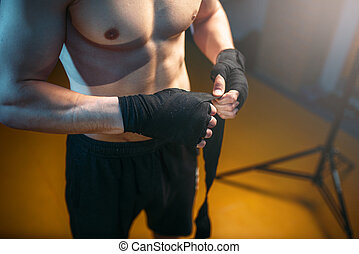 Muscular male person hands in black bandages. Boxing...