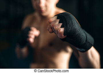 Muscular male person in black bandages. Boxing workout, mens...