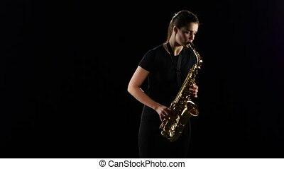 Female plays on the saxophone jazz melody. Black studio...