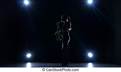 Solo concert of female playing on saxophone. Dark studio,...
