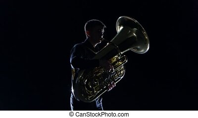 Man plays on the tuba slow melody in black studio - Man...