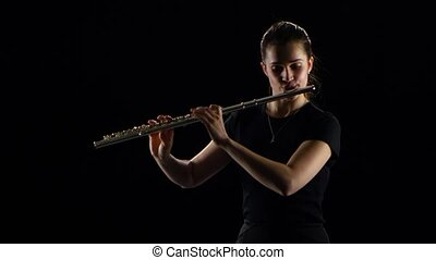 Female plays on the flute classical melodies. Black studio...