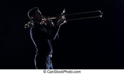 Trumpeter plays on wind instrument fast melody in black...