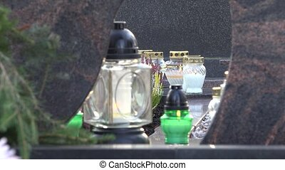 candle light through glass cover on grave in city cemetery....