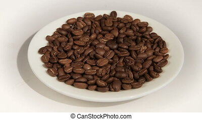 Close up of coffee beans. Loop rotation. Front of the camera rotates white plate with coffee beans