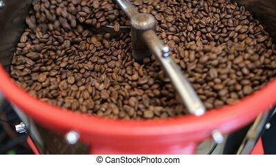 Mixing roasted coffee. Coffee roaster cooling down freshly...