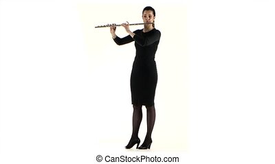 Woman plays on the flute slow melody in white studio - Woman...