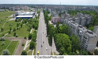 Aerial shot of Kherson city, its multistoreyed buildings, wide street and park
