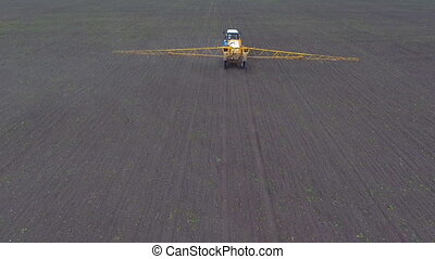 A tractor rides across the field spraying the crop, shooting from the air.