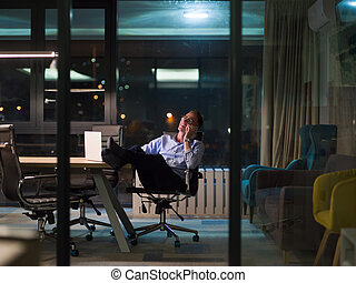 businessman using mobile phone in dark office - Young...