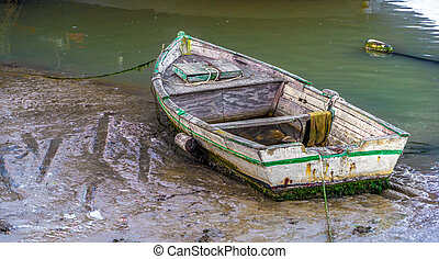 Old Boat in Low Tide - A small fishing skiff sitting in the...