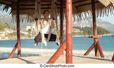 A woman sits in a hammock in a lotus pose on a sunny beach by the sea.