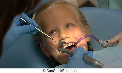 Little girl sitting in the dentists office for examination...